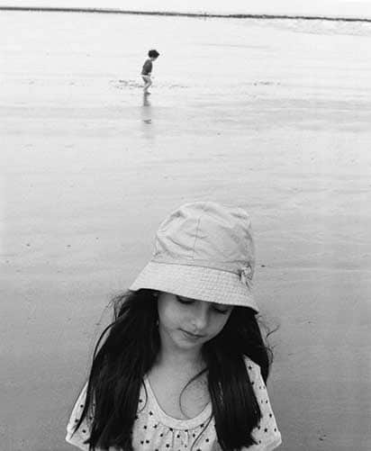 Black and white photo of two children on the beach