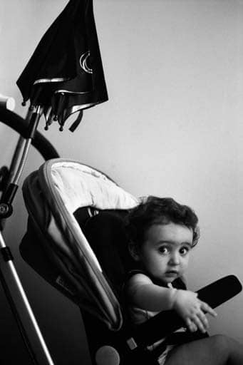 Black and white photo of a child sitting in a pushchair