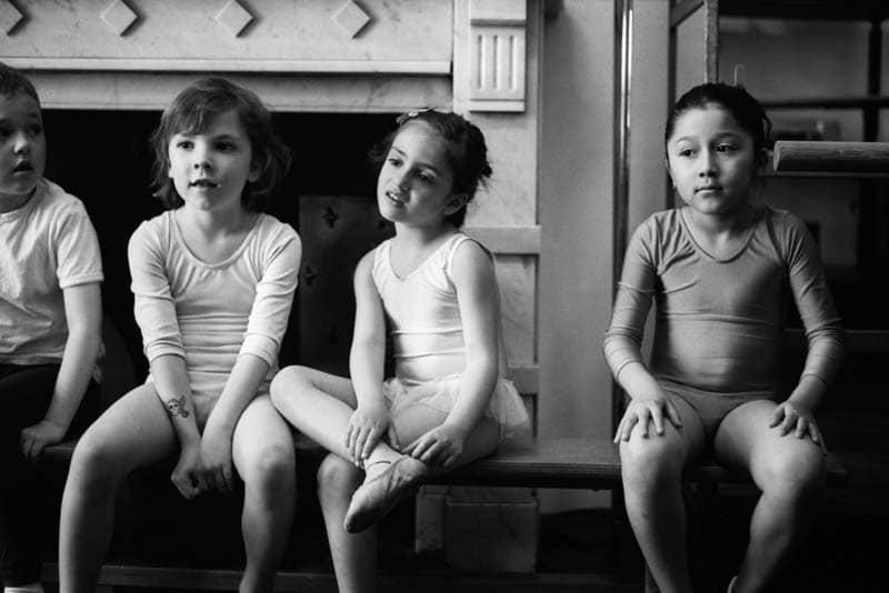 Des enfants attendent sur un banc avant un cours de danse classique