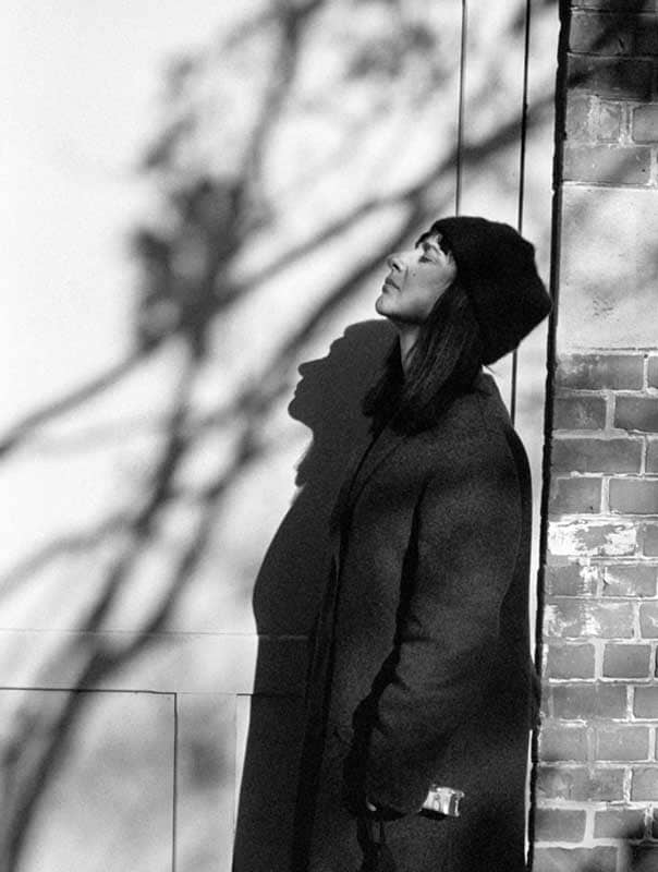 Black and white portrait of a woman against a brick wall and the shadows of trees