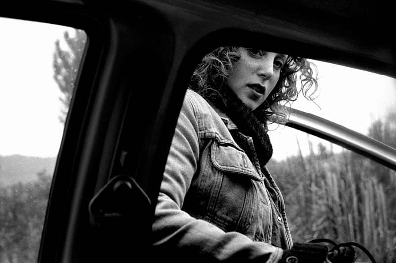 Black and white photo of a woman getting into a car
