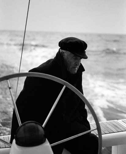 Black and white portrait of a sailor at the helm of a sailing boat