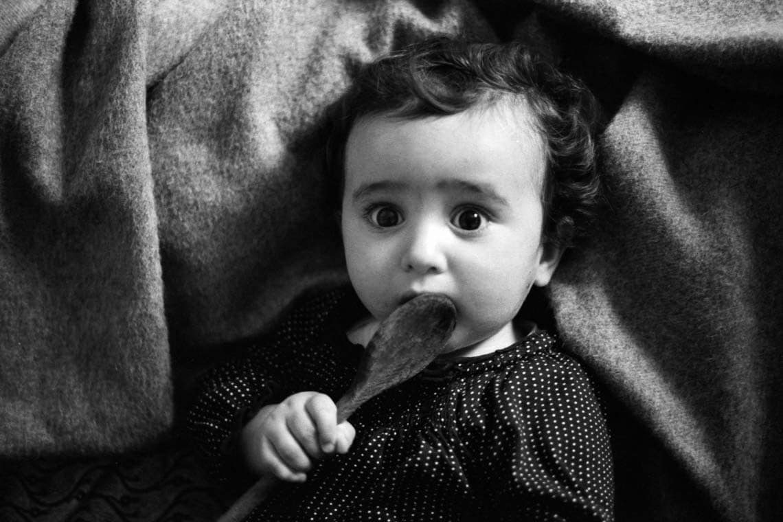 Black and white photo of a baby putting a wooden spoon in its mouth