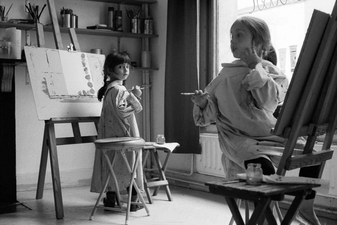 Black and white photo of two children in a painting workshop