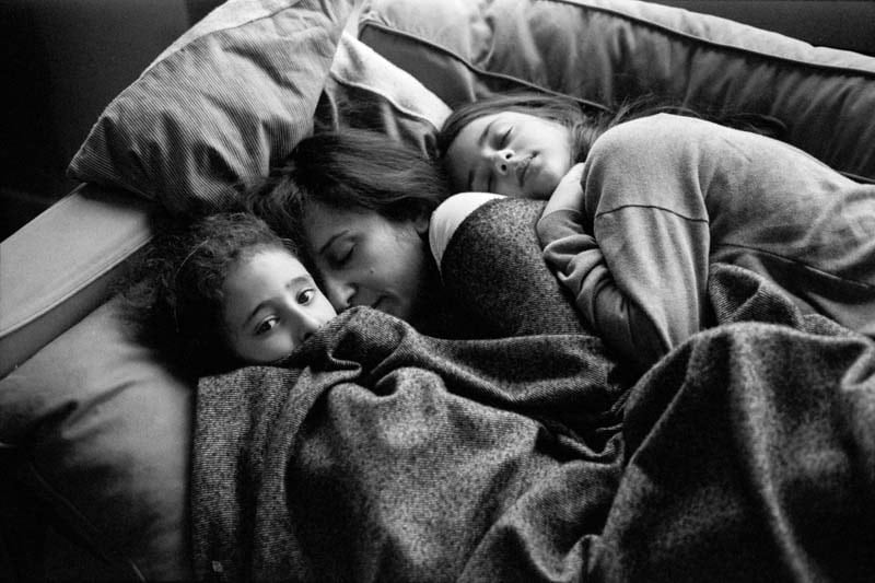Black and white photo of a woman taking a nap with her two children