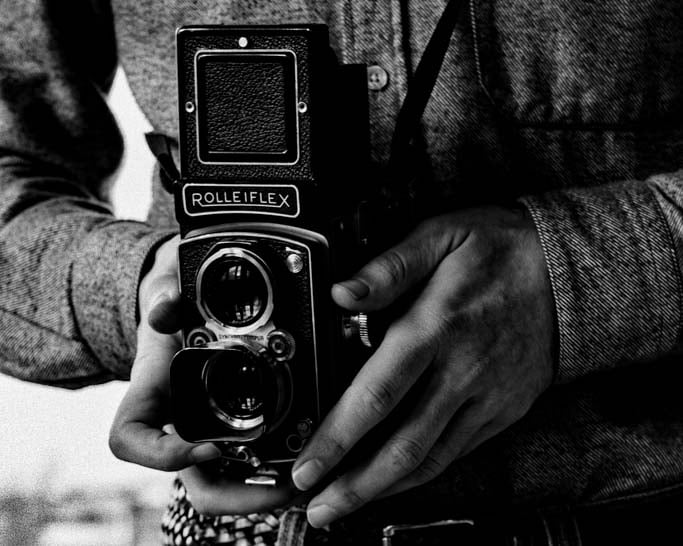 Black and white photo of the photographer and his film camera