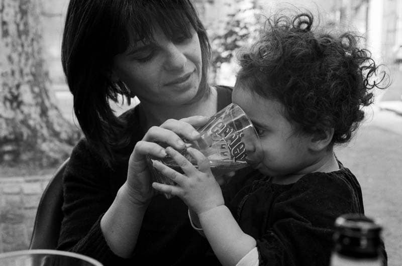 Une maman fait boire un grand verre d'eau à son enfant