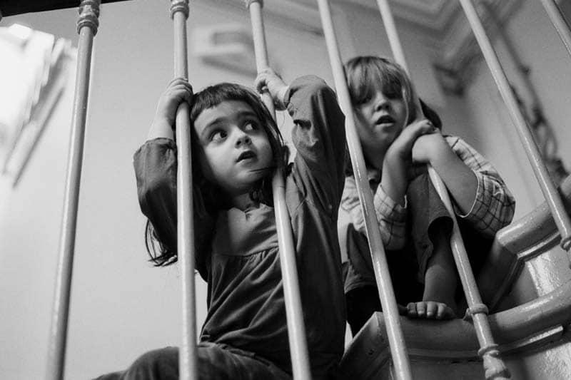 Photo en noir et blanc de deux enfants dans l'escalier