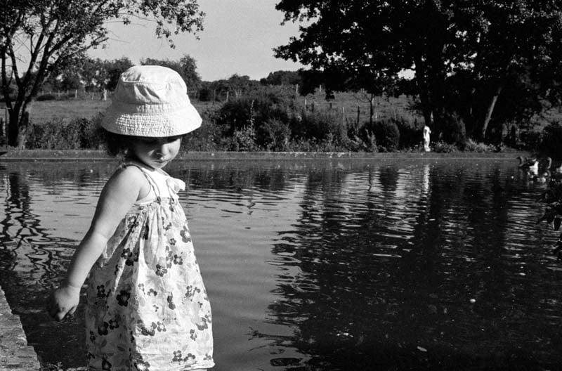 Une fillette est debout au bord d'un étang