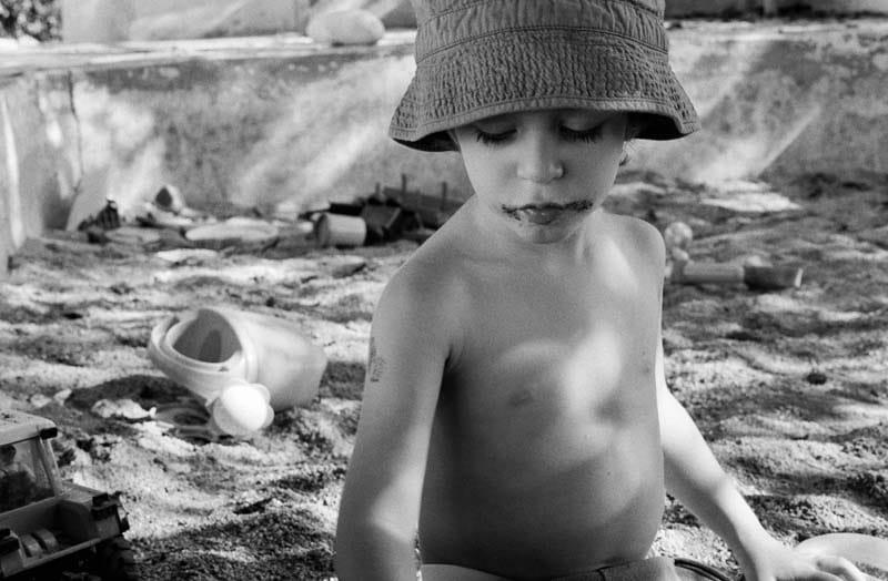 Un enfant est assis dans un bac à sable, un chapeau sur la tête