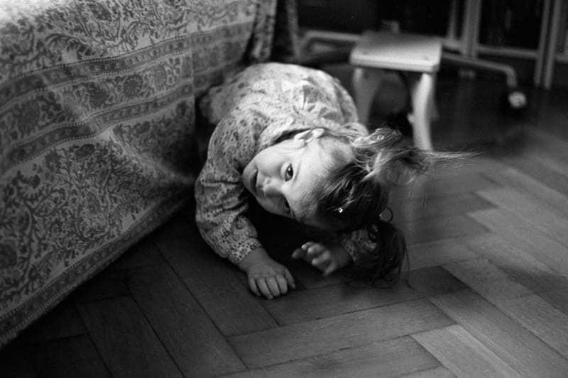 Une enfant est par terre et regarde la personne qui la photographie