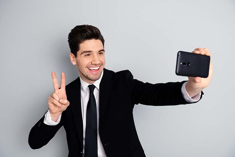 Un homme en costume pose et se prend en photo
