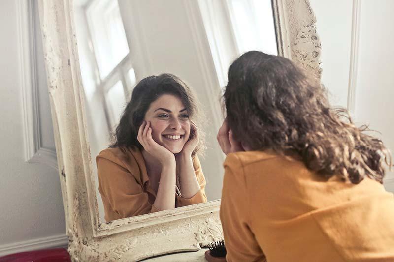 Une jeune femme arbore un large sourire en se regardant dans un miroir