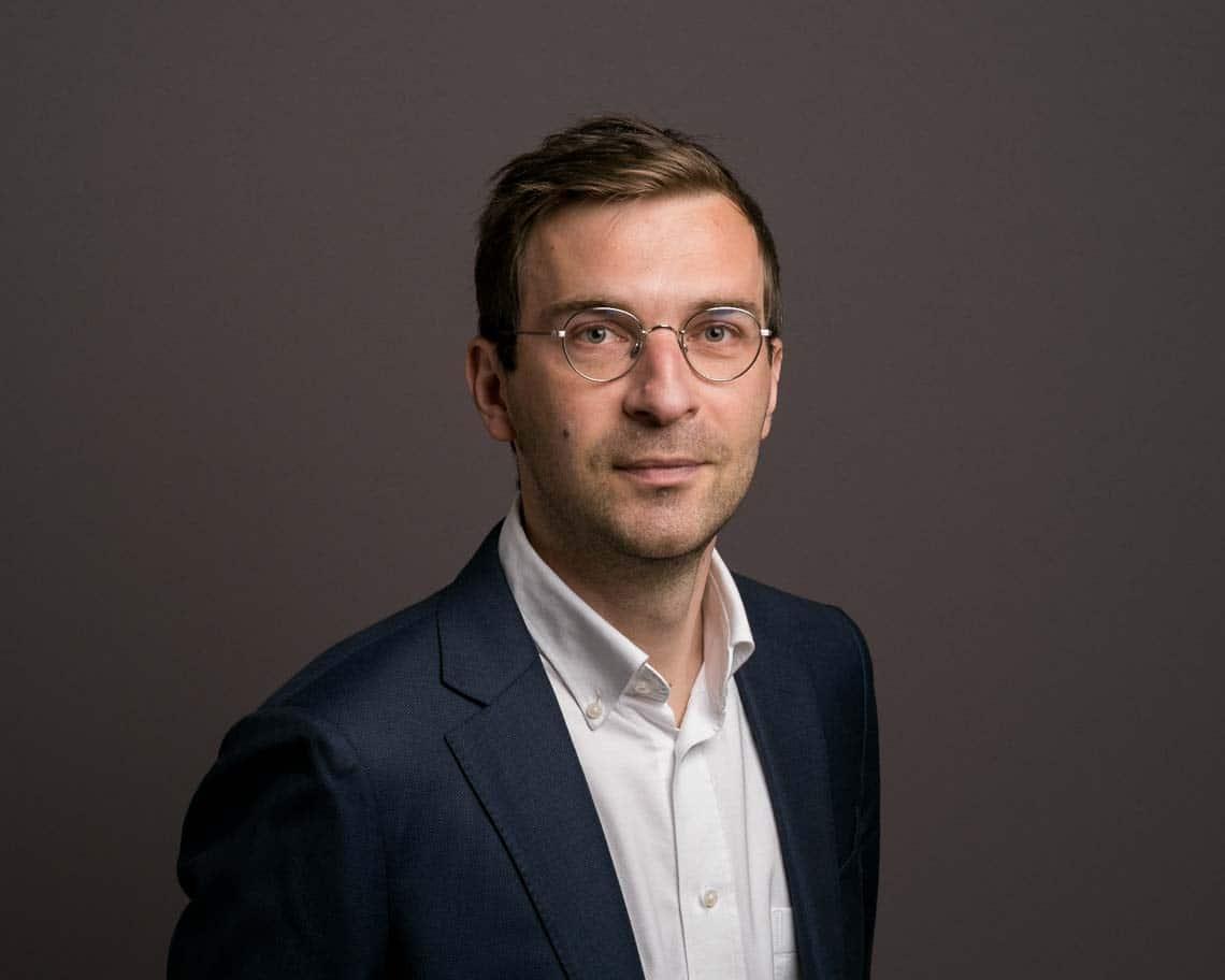 Photo de portrait professionnel d'un homme à lunettes portant une chemise claire et une veste sombre