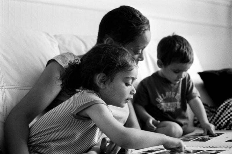 Une maman consulte l'album photo de famille avec ses deux enfants