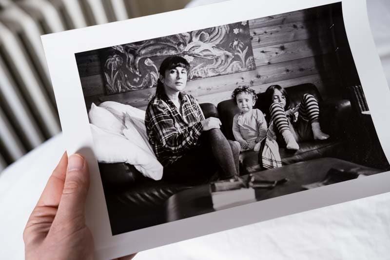 Une main tient une photo de famille en noir et blanc d'une maman et ses deux enfants.