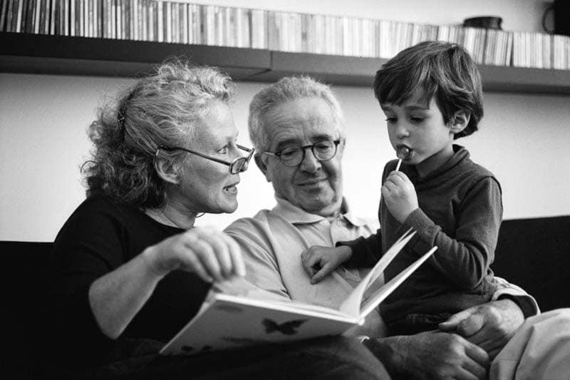 Séance photo de famille, des grands-parents lisent un livre à leur petit fils