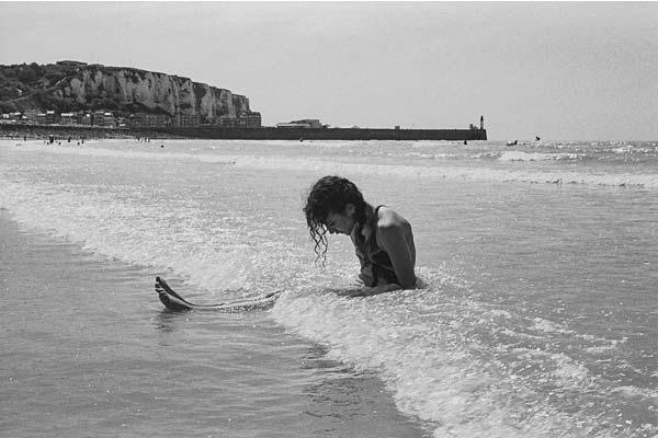 Photo enfant sur la plage, assise dans l'eau