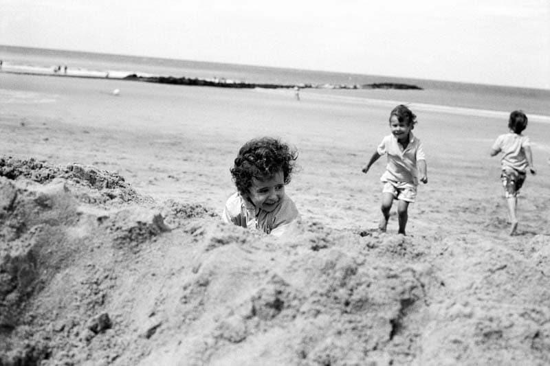 Photo de famille en noir et blanc d'enfants qui courent sur le sable.