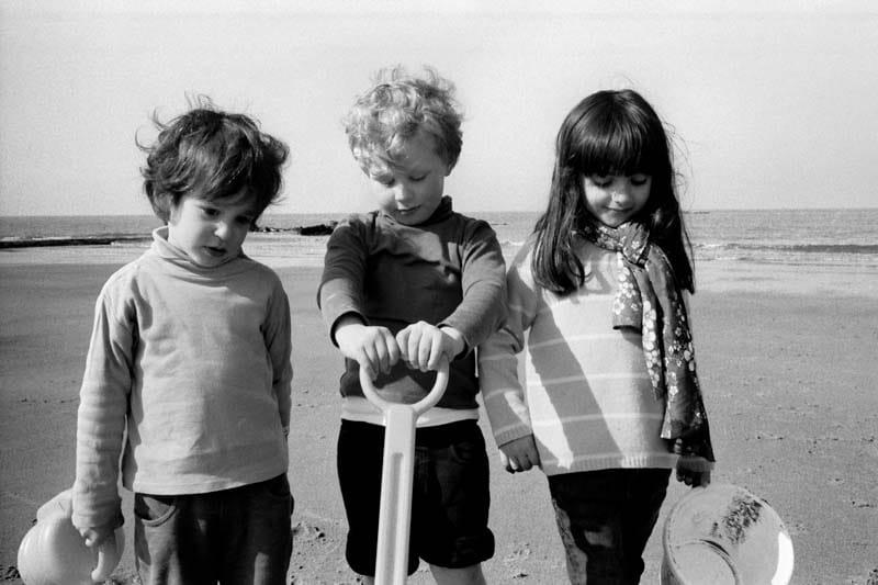 Photo de famille en noir et blanc de trois enfants sur une plage de la mer du Nord