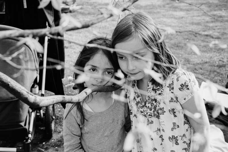 Photo en noir et blanc de deux enfants sous un arbre