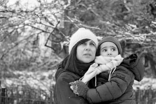 Photo en noir et blanc d'une femme et sa petite fille dans un parc sous la neige