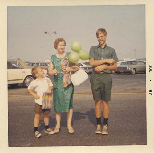 Photo d'une maman et ses deux fils sur un parking faite dans les années 1960