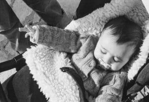 Photo en noir et blanc d'un bébé qui dort dans sa poussette au soleil